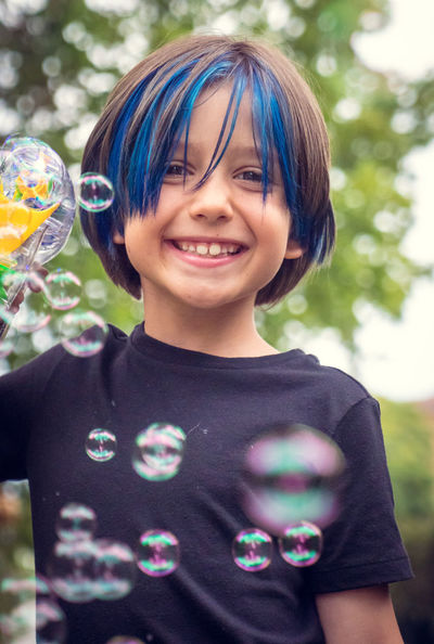 Bubble Gun Bubbles Fun Trees Tshirt Blue Bokeh Boy Bubble Wand Casual Clothing Child Close-up Focus On Foreground Happiness Headshot Leisure Activity Looking At Camera Medium-length Hair Outdoors People Sky Smiling Standing Summer Tree Fashion Stories