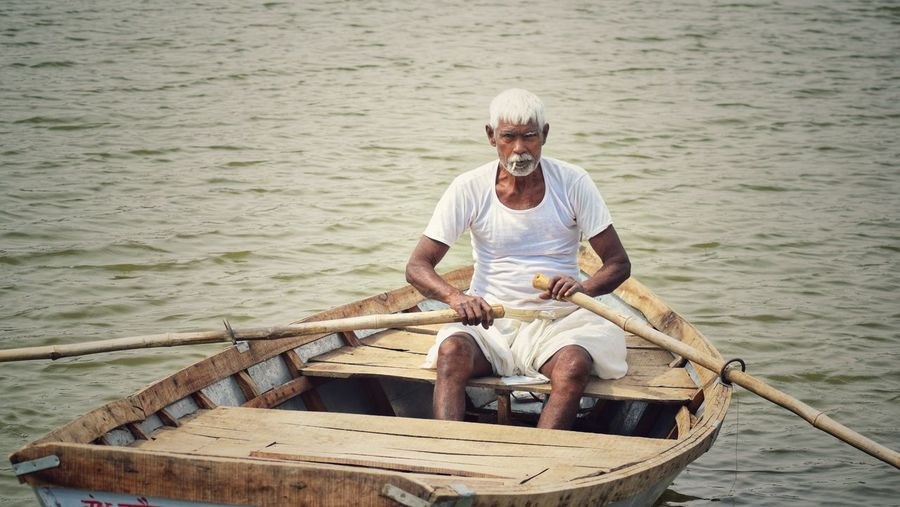 Indian white haired man fishing in pond