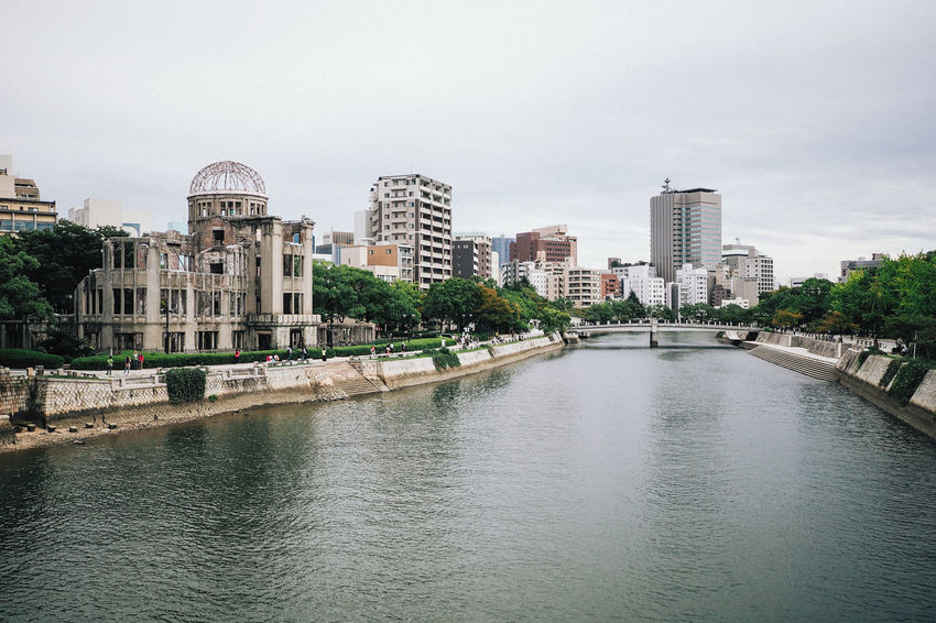 The UNESCO protected Atomic Bomb Dome building and the Ota River in Summertime Architecture Atomic Bomb Building Exterior Built Structure City Cityscape Damaged Day Downtown Emergencies And Disasters Famous Place Hiroshima Peace Memorial Hiroshima Prefecture History Japan National Landmark News Event Old Ruin Outdoors River Skyline Travel Destinations Tree War Water