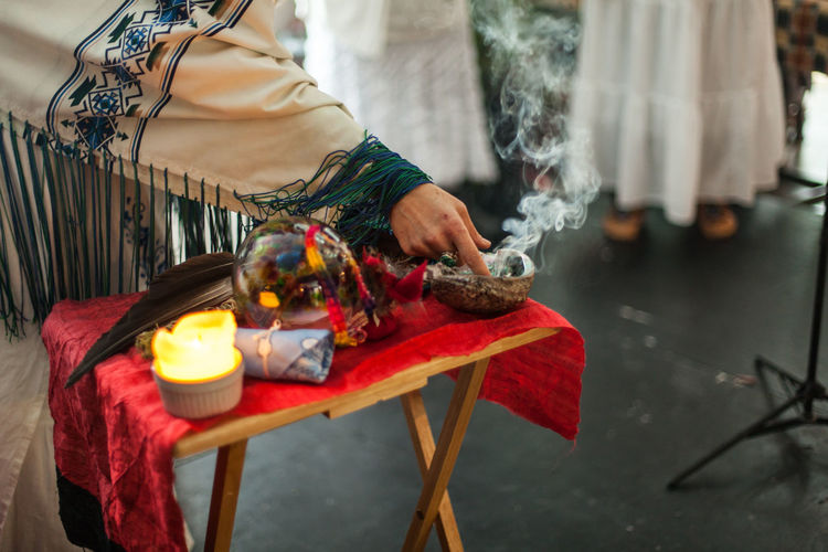 Midsection of man holding lit candles in temple