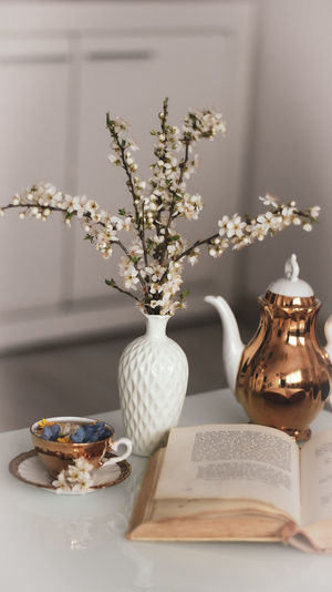 Close-up of white roses in vase on table at home