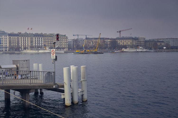 Pier by sea against sky in city