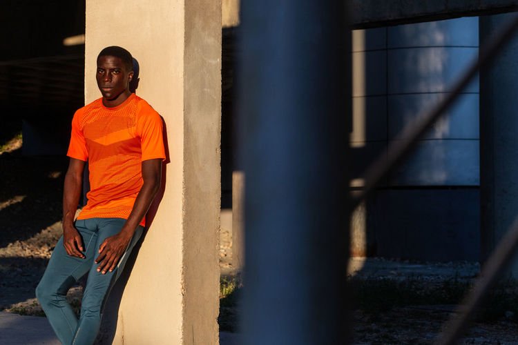 Portrait of young man standing against orange wall
