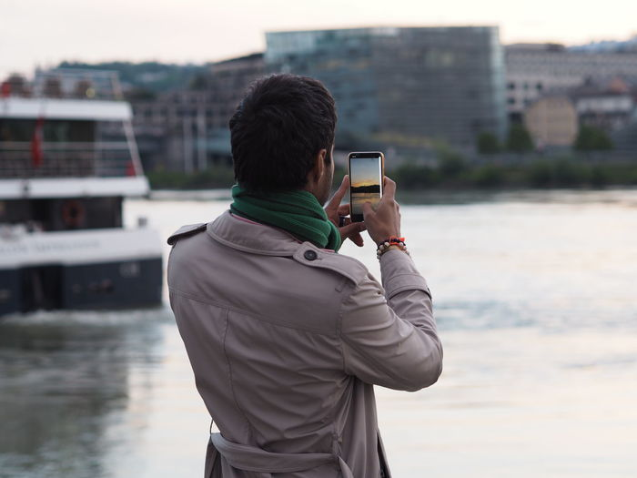 Rear view of man photographing on mobile phone