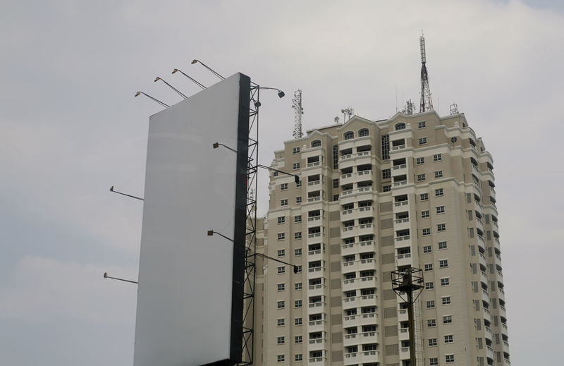 Low angle view of building and billboard against sky
