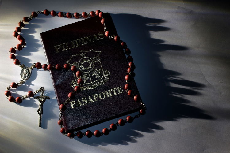 Close-up of passport and rosary on table