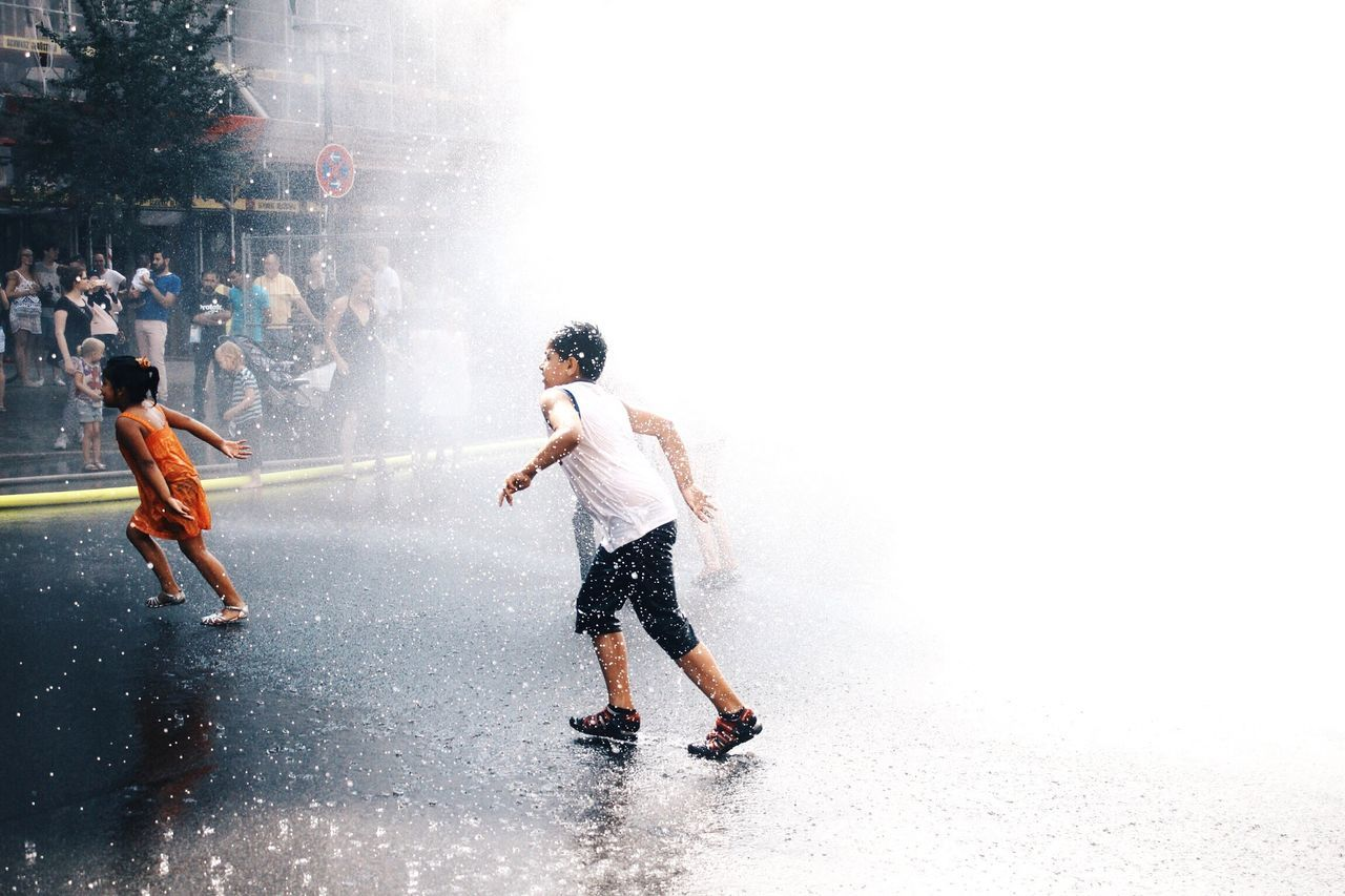 real people, full length, leisure activity, motion, boys, enjoyment, fun, childhood, playing, lifestyles, splashing, casual clothing, water, spraying, togetherness, outdoors, two people, day, men, standing, nature, sky, adult, people