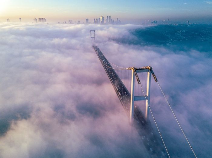 Aerial view of bridge amidst cloudy during sunset