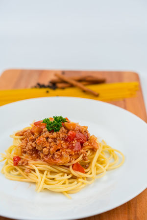 pork spaghetti on white dish placed on wood plate Close-up Delicious Dish Food Food And Drink Indoors  Italian Food Pasley Pork Ready-to-eat Reataurant Spaghetti Wood - Material