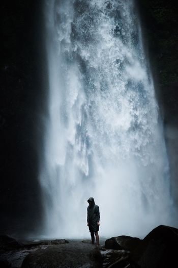 Man standing on rock against waterfall