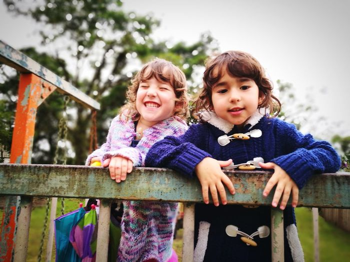 Portrait Of Happy Girls Standing By Railing At Park Against Sky