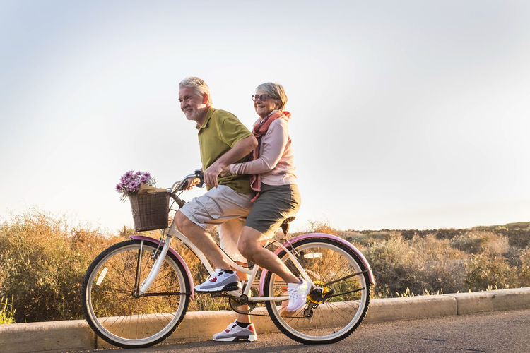 two senior man and woman together on an old bicycle outdoor activity Complicity Having Fun Adult Bicycle Couple - Relationship Elderly Couple Emotion Enjoying Life Freedom Full Length Happiness Leisure Activity Lifestyles Males  Men Nature Positive Emotion Retired Person Riding Sky Smiling Sunlight Togetherness Transportation Two People