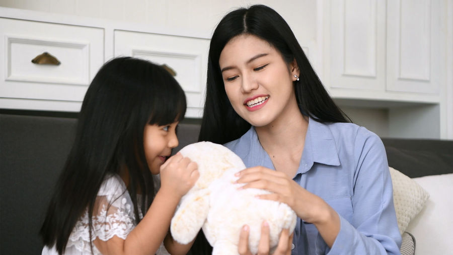 Family concept. The mother is teasing the daughter in the living room. Activity Apartment ASIA Attractive Beauty Cheerful Children Converse Couple Cute Daughter Delight  Development Doll Elementary Enjoy Face Family Favor Fun Happy Hug Ingratiate Jolly Kid Kiss Lady Lifestyle Like Little Girl Mom Motherhood Nanny Parent People Play Puppet Rest Room Smile Sofa Talk Tease Teddy Bear Thailand Together Toy Vacation Want Women Young Adult