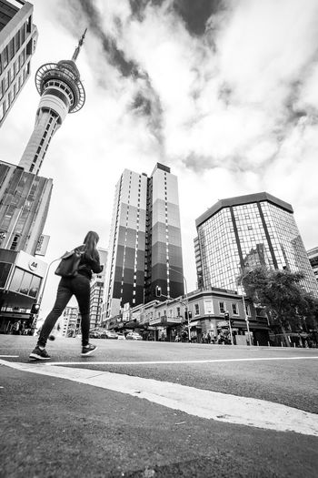 young woman walking over a street Auckland Travel Architecture Black And White Building Building Exterior Built Structure City City Life Financial District  Low Angle View Nature New Zealand Office Office Building Exterior People Real People Road Sky Skyscraper Spire  Street Streetphotography Tall - High Tower The Street Photographer - 2018 EyeEm Awards