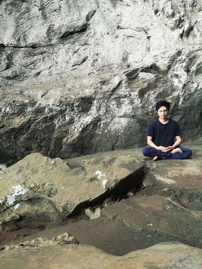 Portrait of woman sitting on rock