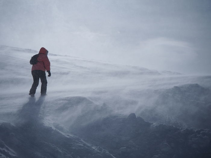 Rear view of man on mountain against sky during winter