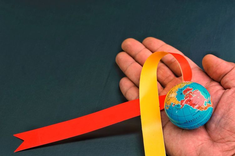 Cropped hand holding globe and ribbon