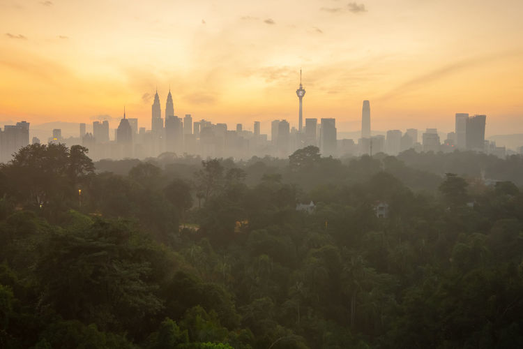 Kuala Lumpur skyline sunrise Built Structure Architecture Building Exterior Sunset Sky City Building Cityscape Orange Color No People Plant Nature Skyscraper Fog Tree Urban Skyline Landscape Office Building Exterior Cloud - Sky Tower Outdoors Pollution