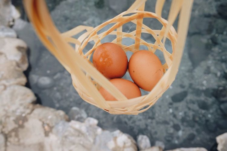 Close-Up Of Eggs In Wicker Basket Hanging Over Pond