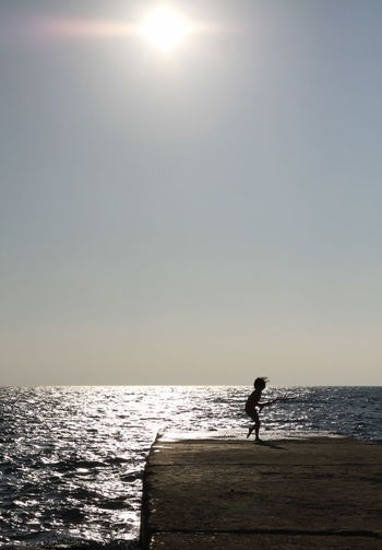 Playing child Beach Child Childhood Memories Clear Sky Day Horizon Over Water Lifestyles Nature One Person Outdoors Real People Scenics Sea Silhouette Sun Sunlight Water