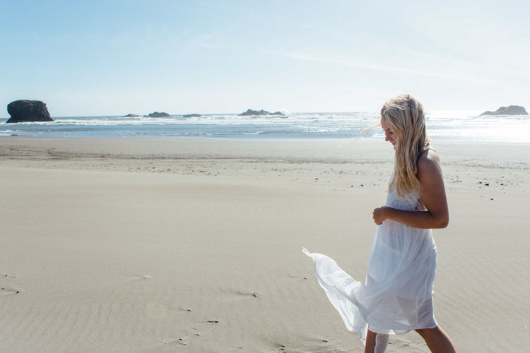 Side View Of Smiling Young Woman Walking On Beach Against Clear Sky