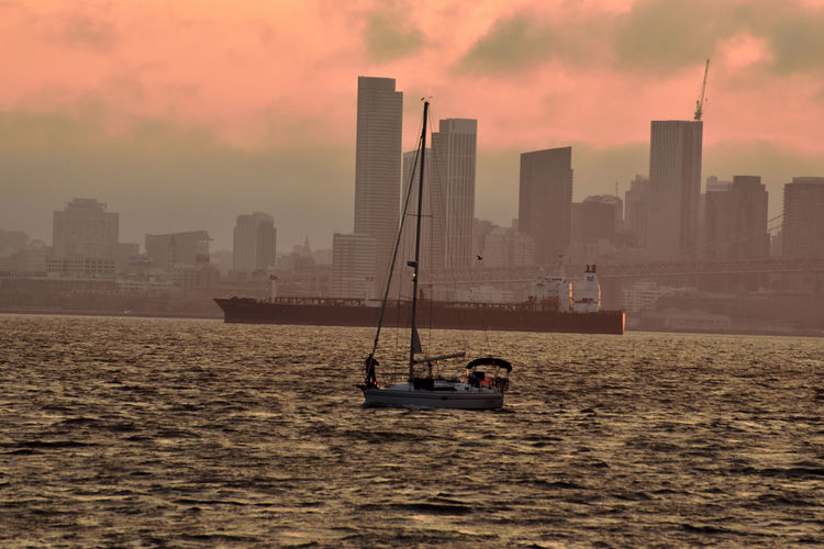 Ship in sea against buildings during sunset