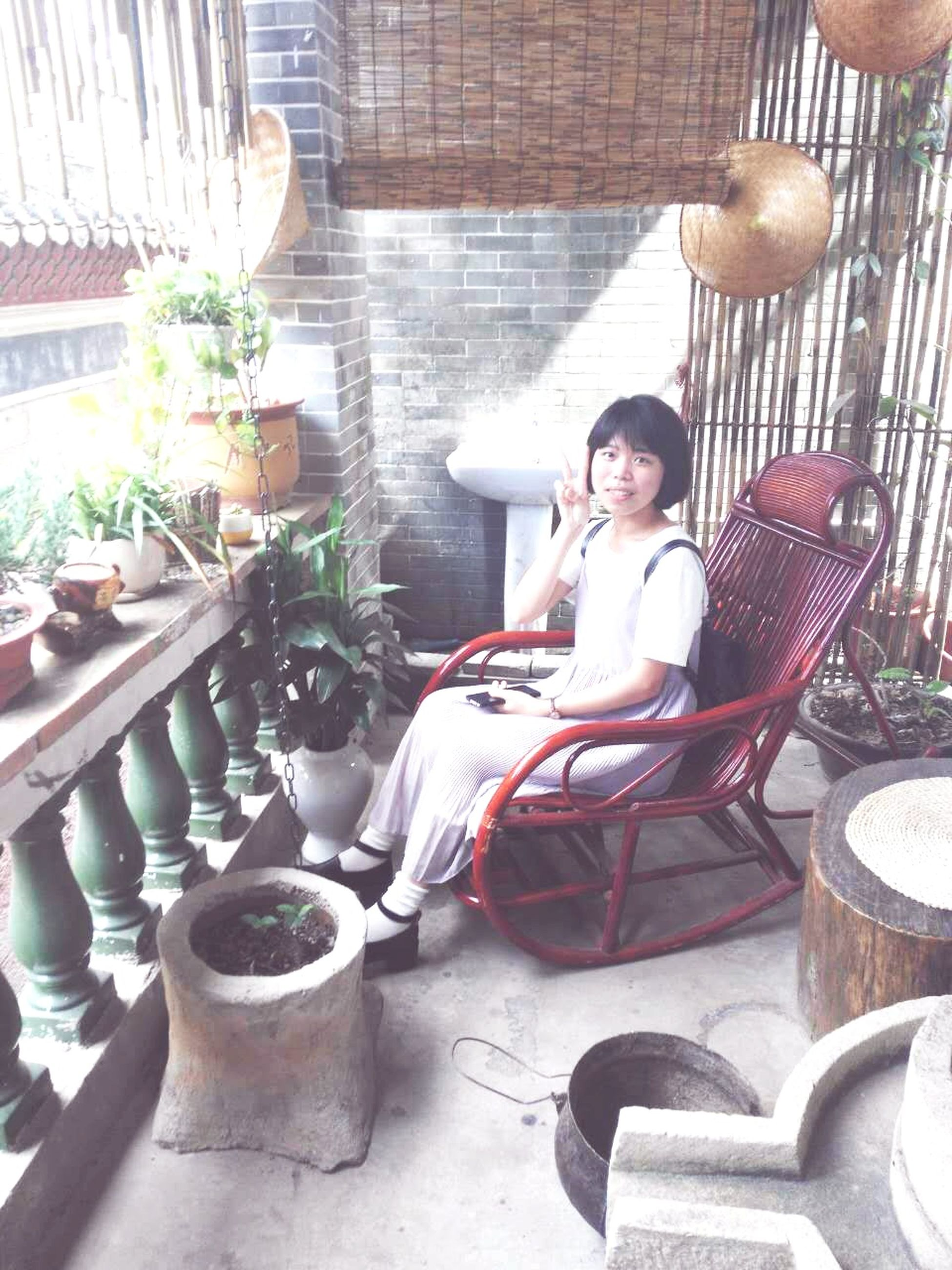 sitting, indoors, lifestyles, chair, casual clothing, table, person, leisure activity, sunglasses, food and drink, drink, young adult, potted plant, standing, day, front view, high angle view, relaxation