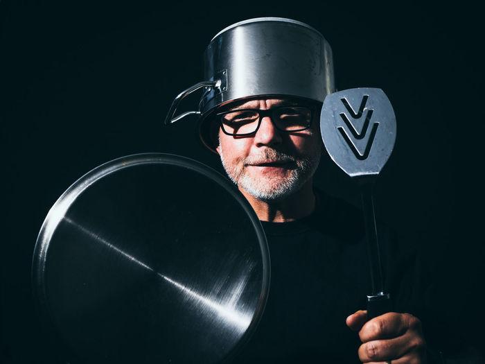 Portrait of man holding eyeglasses against black background