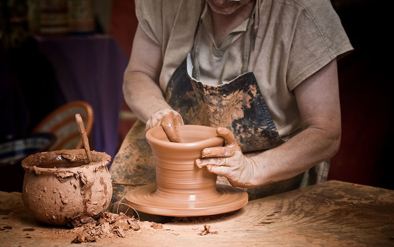 Midsection Of Man Making Pot On Wheel
