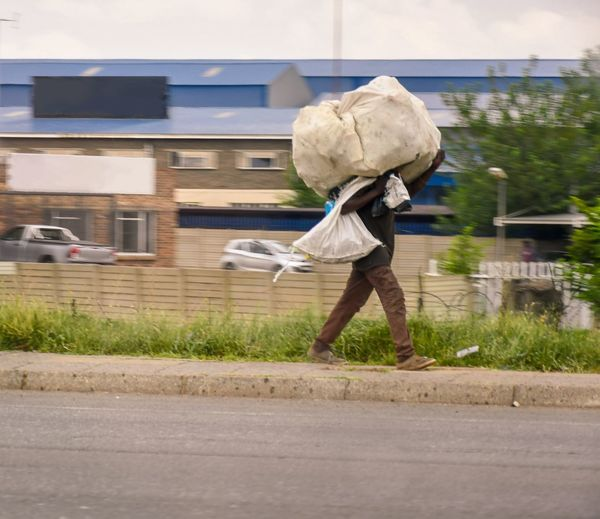 Man carrying his luggage on his head. Outside Clothing Tree Family Road person Growth Strange Young Adult Bag People One Person Man Luggage Adult Outdoors Lifestyles Travel Day Portrait Summer Activity Motion Walking Colors Sunlight Grass Clear Sky Full Length Sky