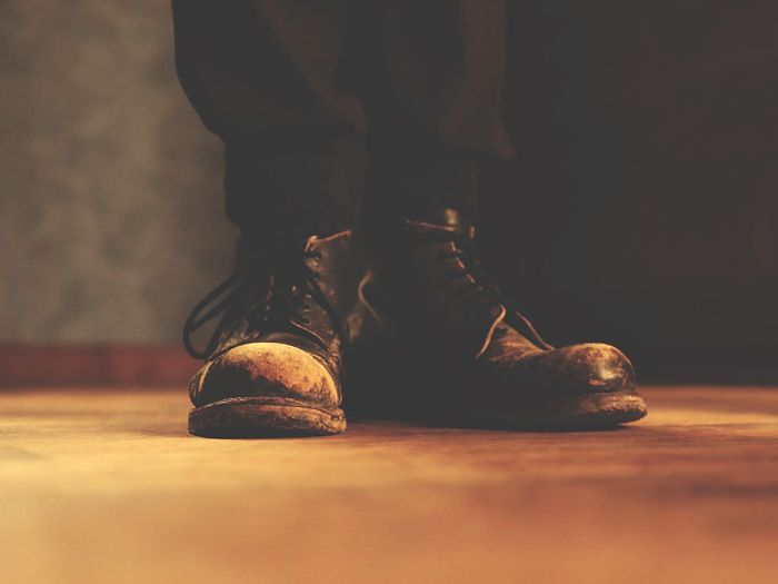 Low section of man wearing boots standing on floor