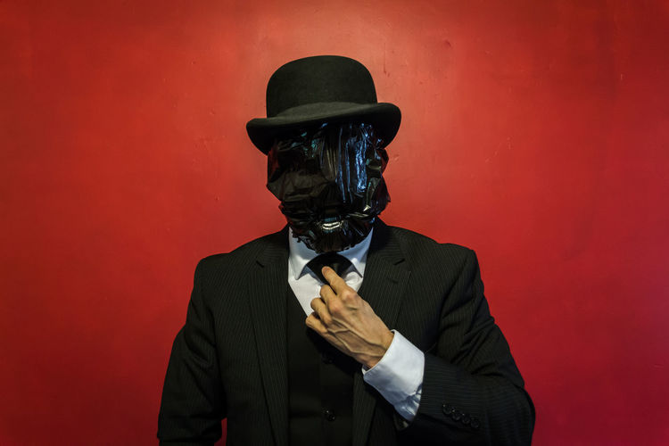 Businessman covering face with plastic while wearing hat against red wall