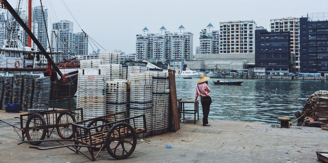Rear View Of Man Standing By Crates Against Lake In City