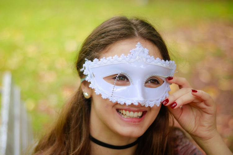 Smiling Young Woman Wearing Venetian Mask