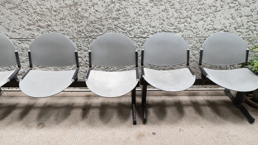 Close-up of empty chairs against wall