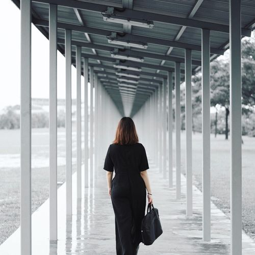 Rear View Of Woman Walking In Walkway