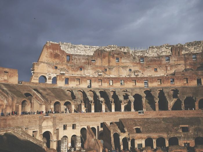 Old ruins of colosseum against overcast sky