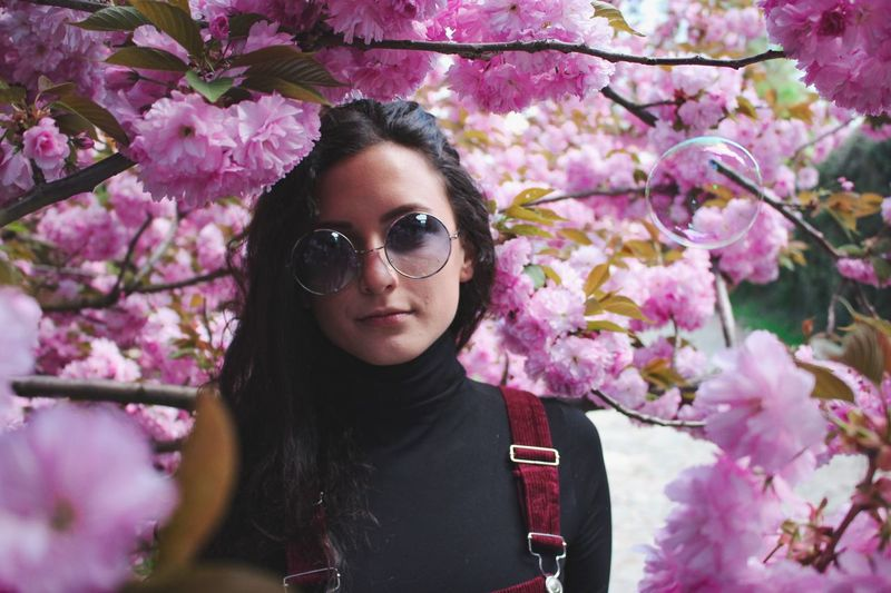 Portrait of beautiful woman amidst pink flowers