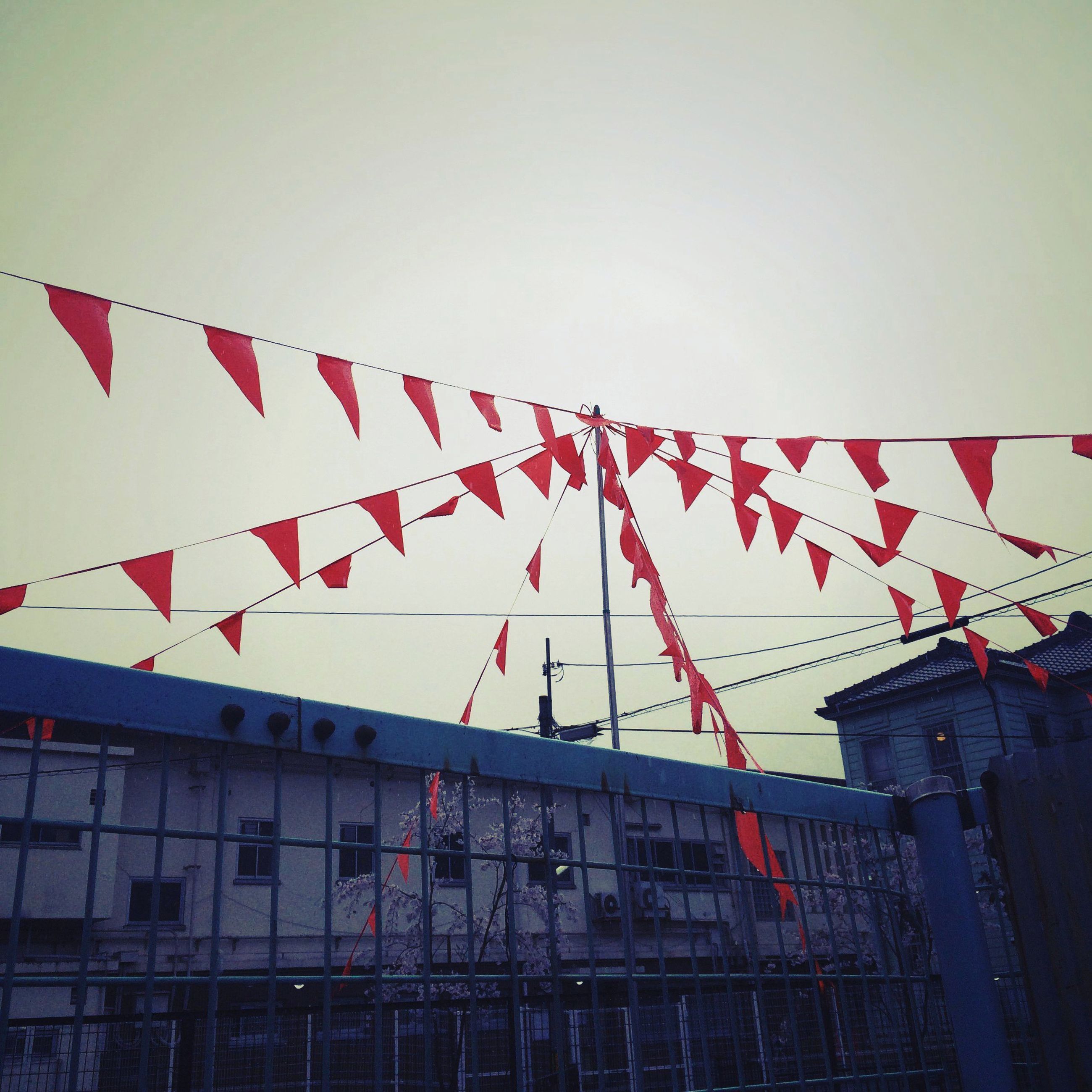 architecture, building exterior, built structure, low angle view, clear sky, flag, red, hanging, building, city, identity, national flag, patriotism, sky, outdoors, day, residential building, no people, residential structure, decoration