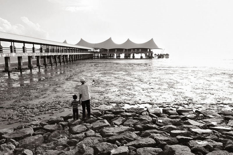 A grandfather and grandson love in front of Kuala Perlis watching over a Sunset Father Father & Son Full Length Grandfather And Grandson Granfather Horizon Over Water Jetty Leading Light Long Love Lovely Outdoors Pier Railing Sea Water Wood Wood - Material Wooden Post