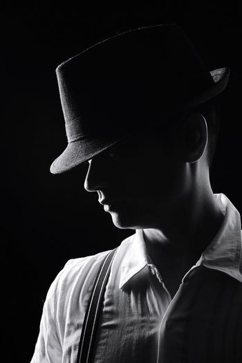 Close-Up Of A Man Wearing Hat Over Black Background