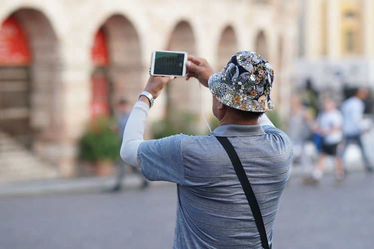 Rear view of man photographing with smart phone while standing on street