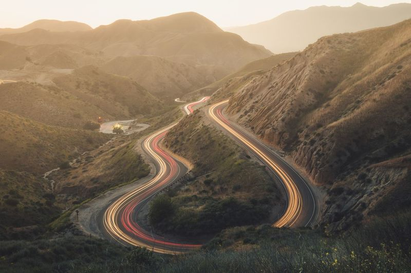 High angle view of light trails on winding road on mountain