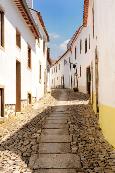 Typical street scene in a medieval city. Marvao, Portugal EyeEmNewHere Alley Architecture Building Exterior Built Structure Cobblestone Day No People Outdoors Residential Building Sky The Way Forward Walkway Window