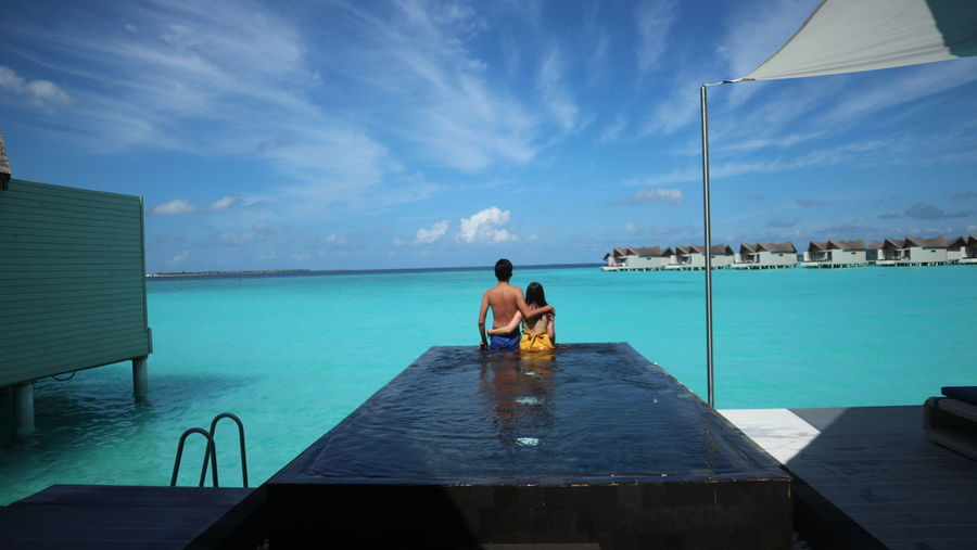 Rear view of couple standing in infinity pool