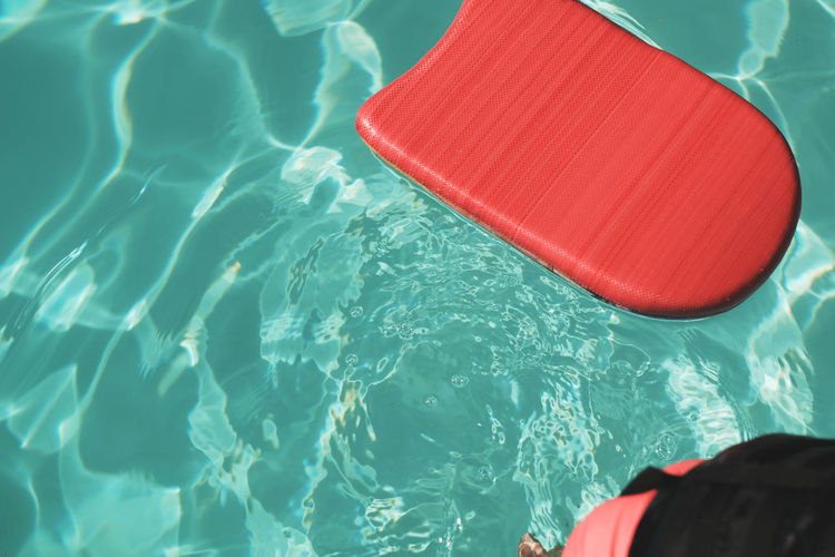 High angle view of red pool raft floating on swimming pool during sunny day