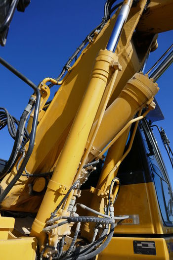 Low angle view of earth mover against clear sky