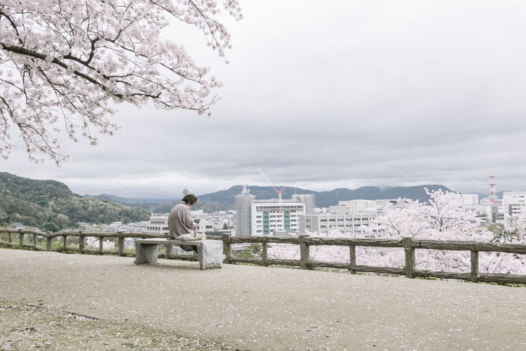 Man Sitting On Bench At Observation Point By City Against Sky