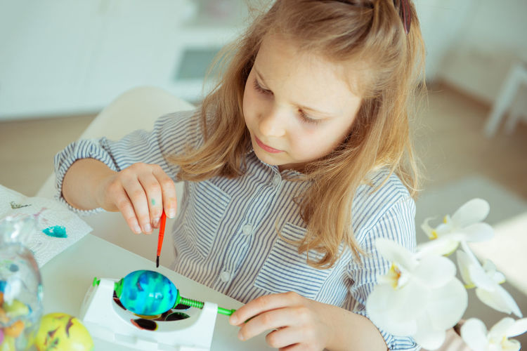 Cute girl painting easter egg while sitting at home
