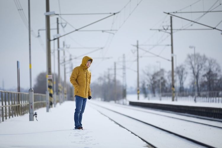 Full length of person on snow covered railroad tracks during winter